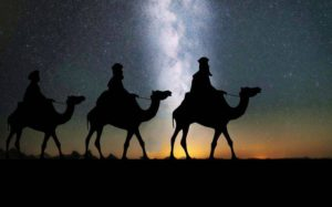 Three kings travelling against a starry sky
